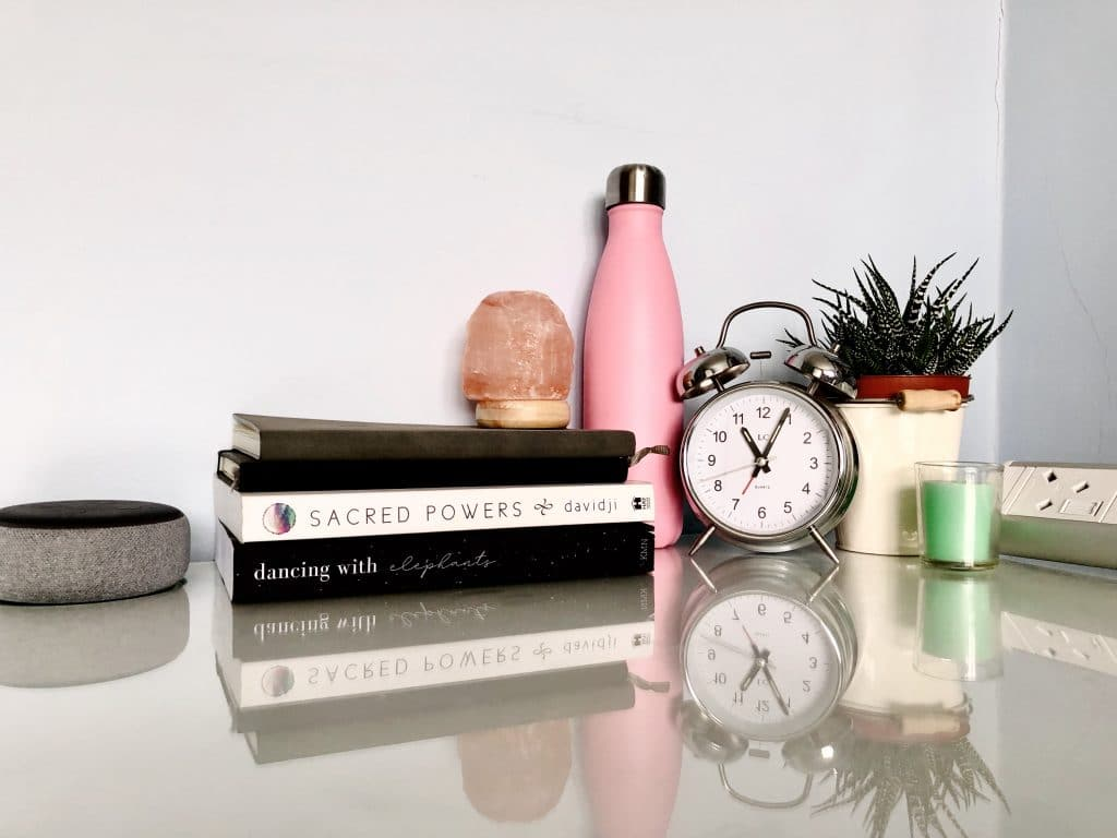 Organise your life: Water bottle, clock, plant, books, speaker Alexa, notepads and journals, salt lamp, candle on desk for working from home. Organise your life: My GYST routine and how to create your own