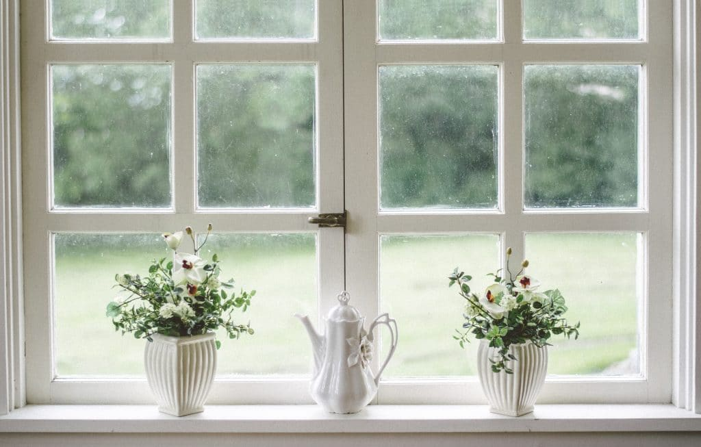 The ultimate spring cleaning checklist - white windows looking out into garden with plants and watering can sat on the window sill